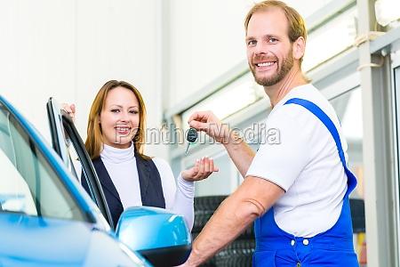 kundin und mechaniker an auto in