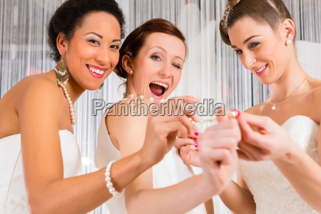 women with fun trying on wedding