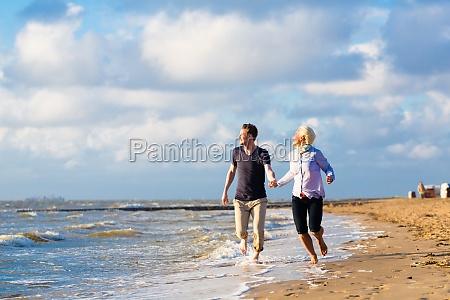paar rennt durch wellen und sand