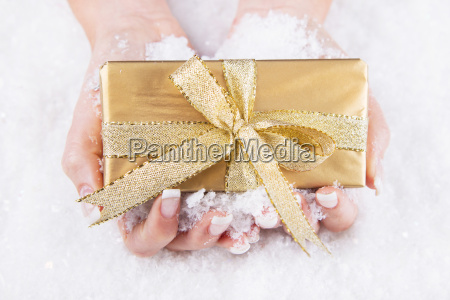 woman is holding a golden christmas