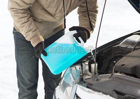 nahaufnahme des menschen giessen frostschutzmittel in