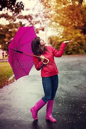 glueckliche frau mit regenschirm fuer regen