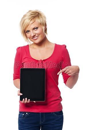lächelnde, blonde, frau, zeigt, auf, bildschirm - 12112236