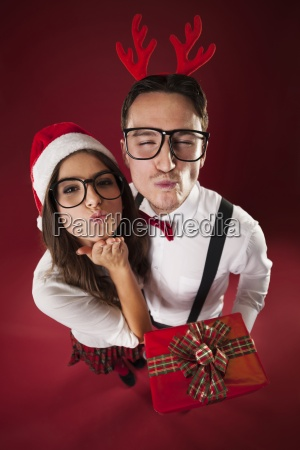 nerd couple blowing kisses in christmas