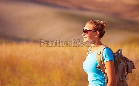 beautiful traveler girl enjoying golden wheat