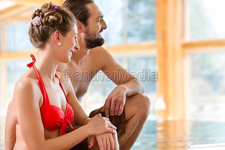 paar sitzt am pool eines wellness