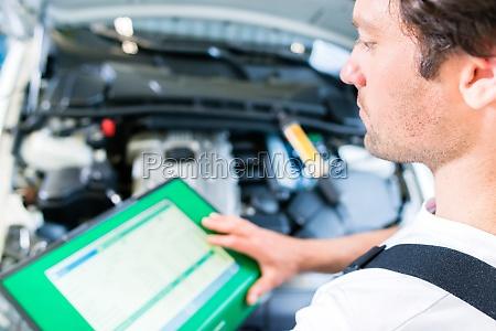 kfz mechaniker mit diagnosegeraet in autowerkstatt