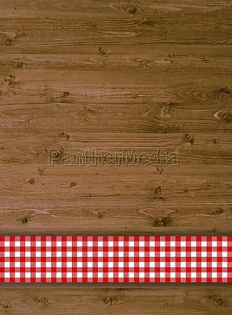 rustikaler holzhintergrund mit tischdeckenstreifen rot