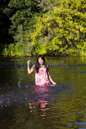 young japanese woman splashing river dress
