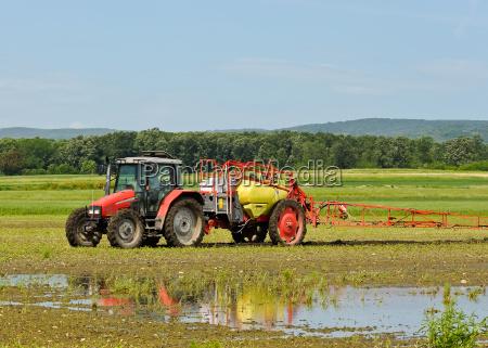 landwirt duengt das feld mit traktor