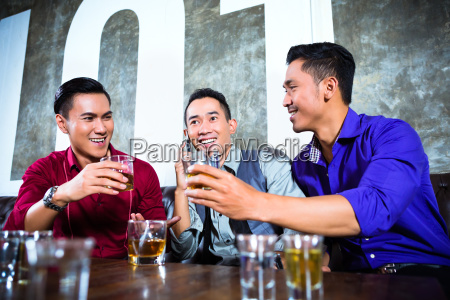 asiatische freunde die schuesse im nachtklub