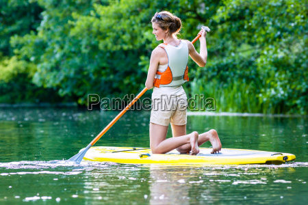 woman while standing paddling sup on
