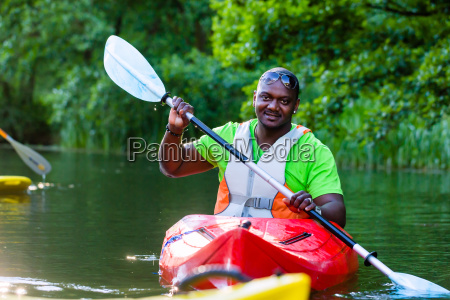 african man was traveling by kayak