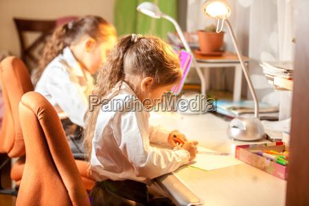 kleine maedchen zeichnen bilder hinter schreibtisch
