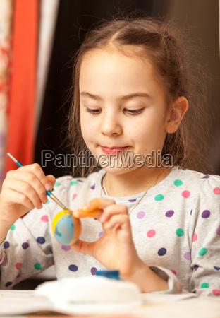 maedchen malen traditionelle ostereier zu hause