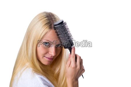 frau kaemmt sich die haare mit