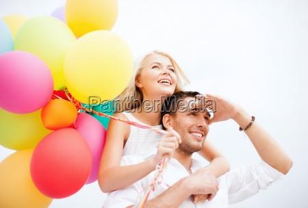 paar mit bunten luftballons an der