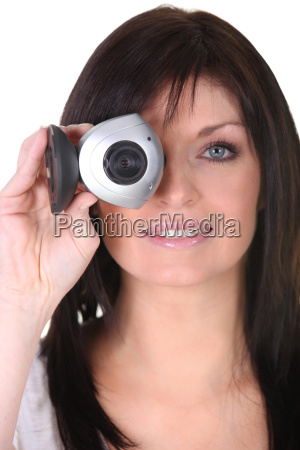 young woman holding webcam on white
