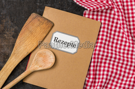 recipe book with wooden spoons on