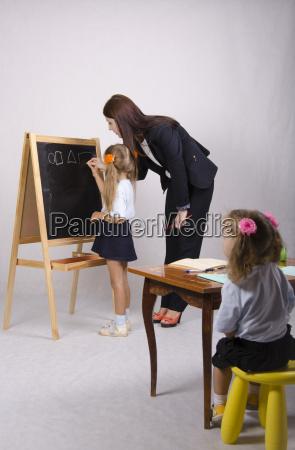 auf tafel maedchen mit lehrer zeichnen