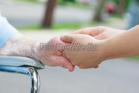 caregiver halte aelteren womans hand