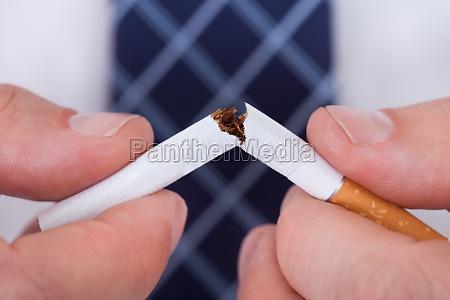 man hand die zigarette bricht