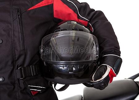 mann in schutzkleidung mit seinem motorrad