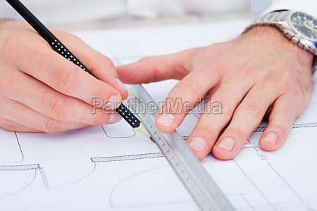 architect drawing on blueprint