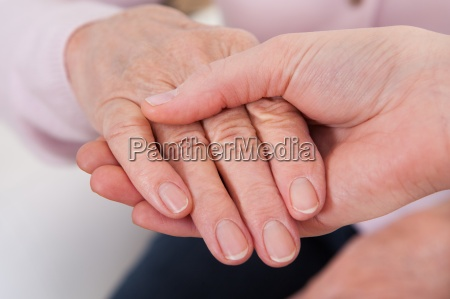 young woman holding senior womans hand