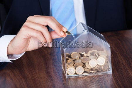 businessman inserting coin in box