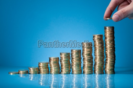 hand placing coin on stack of