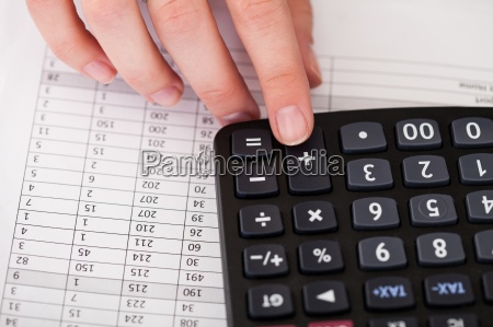 close up of hand with calculator