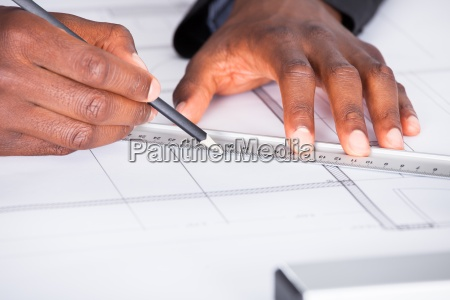 architect with blueprint in office