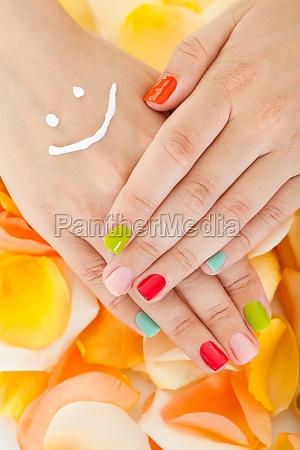womans hand above flower petals