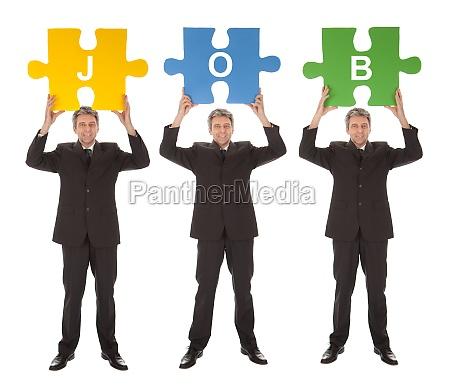 gruppe von geschaeftsleuten die puzzle halten