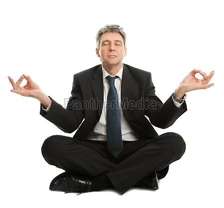 kaufmann sitzt in yoga position