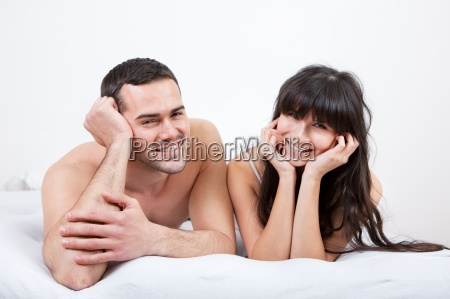 young couple lying up in bed