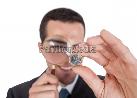 businessman looking at one euro coin