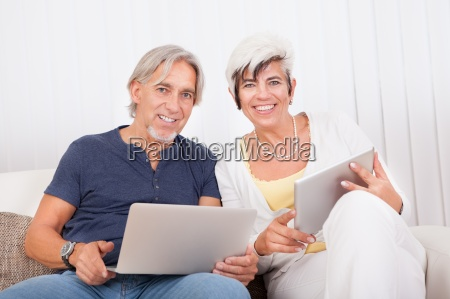 happy couple at home using laptop