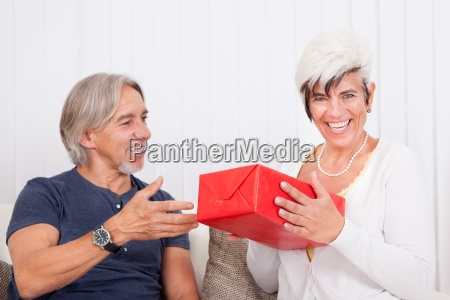 laughing senior couple with red gift