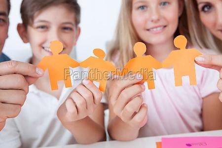familie die in der hand papierleute