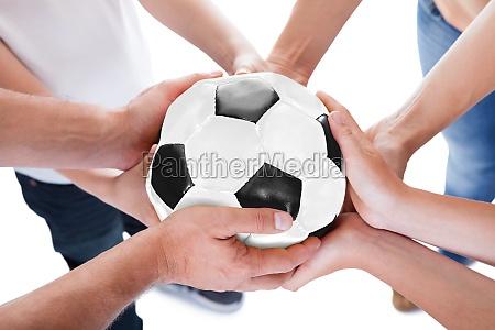 several hands holding together soccer ball