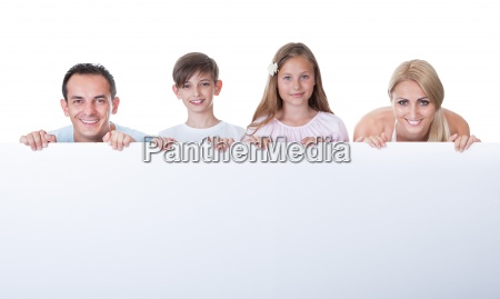 portraet der familie hinter blank board