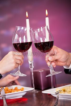 close up of couple toasting wine