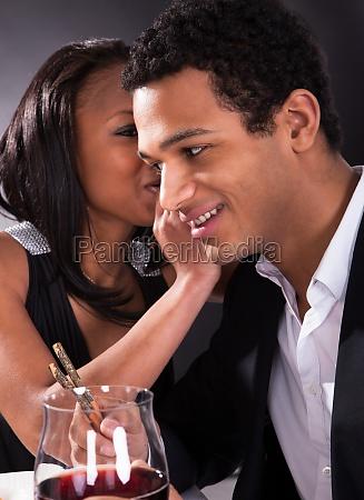 woman whispering to boyfriends ear