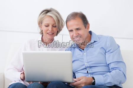 happy mature couple working on laptop