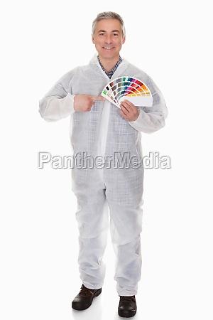reifer mann mit schuetzender arbeitskleidung holding