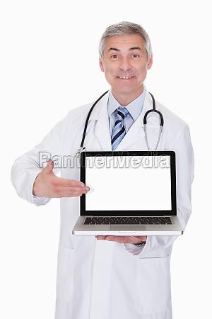portrait of male doctor showing laptop