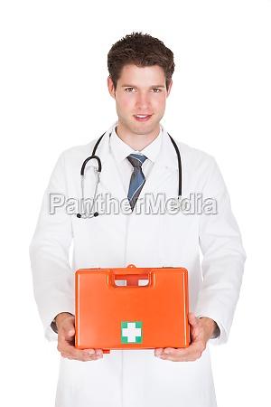 doktor holding erste hilfe box