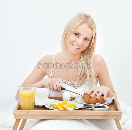 beautiful woman cutting croissant